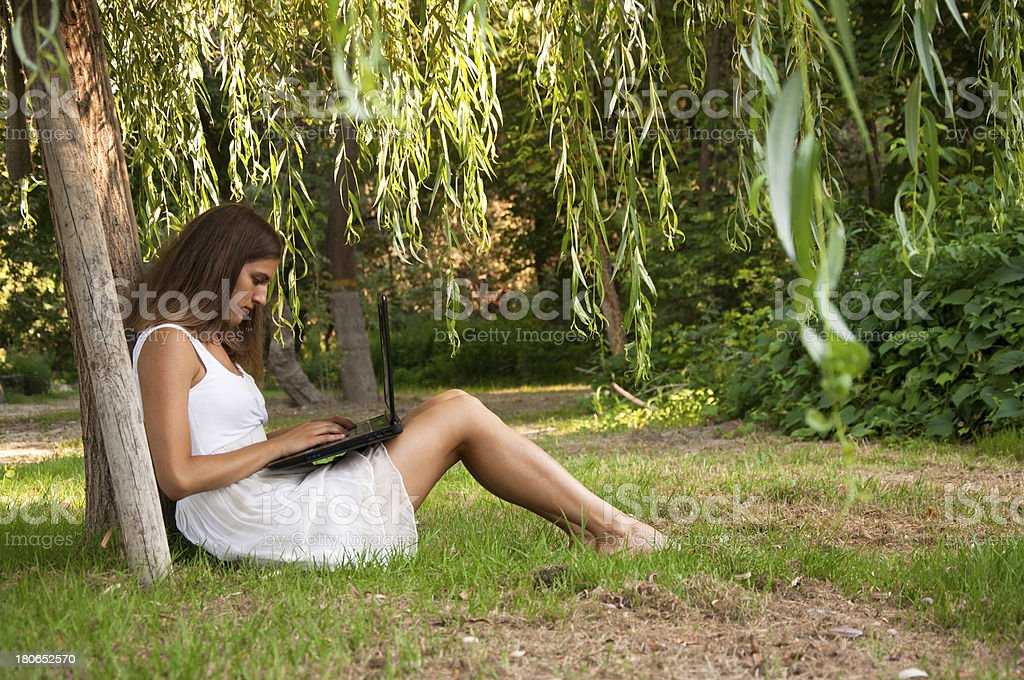 Beautiful young girl using laptop outdoors royalty-free stock photo