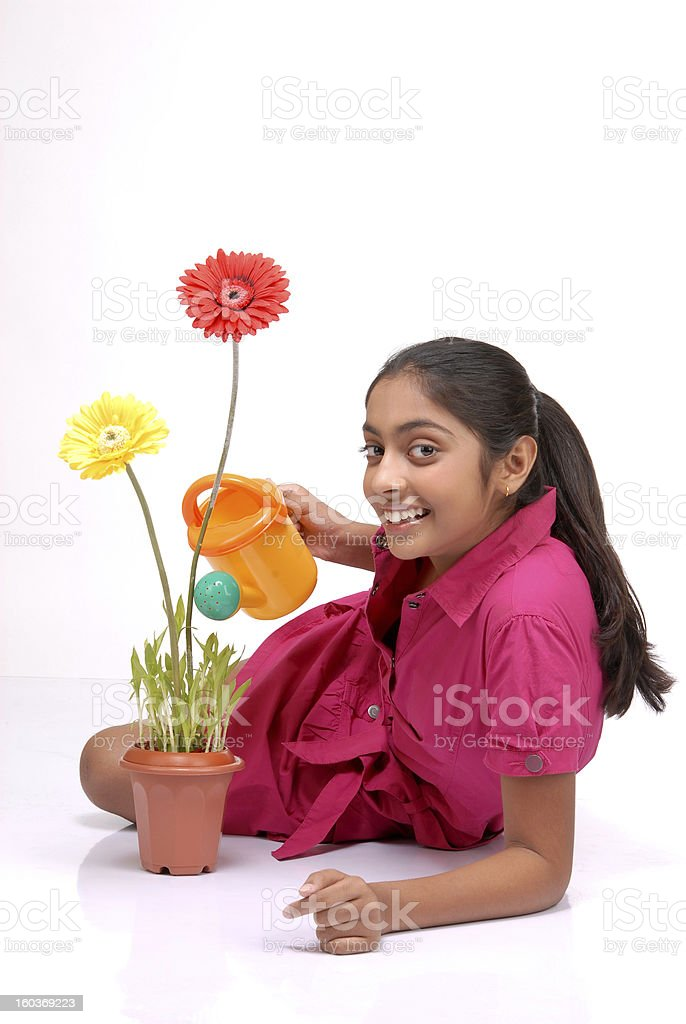 Beautiful young girl watering a plant royalty-free stock photo