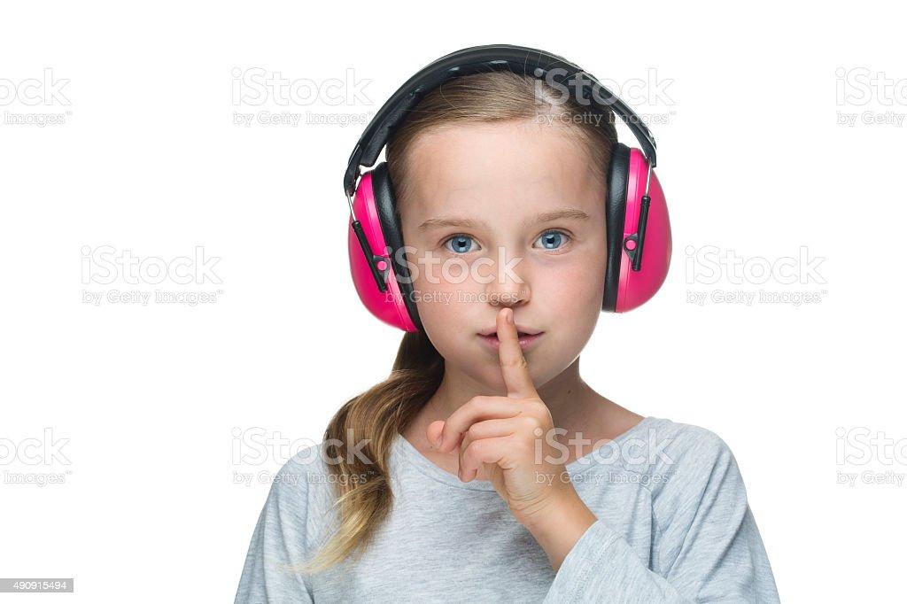 Beautiful young girl wearing pink earmuffs stock photo