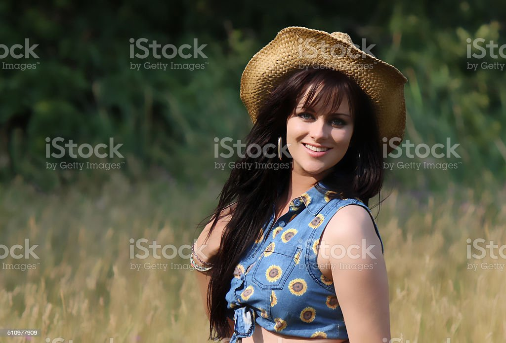 Beautiful Young Girl with Black Hair, Wearing a Straw Hat stock photo