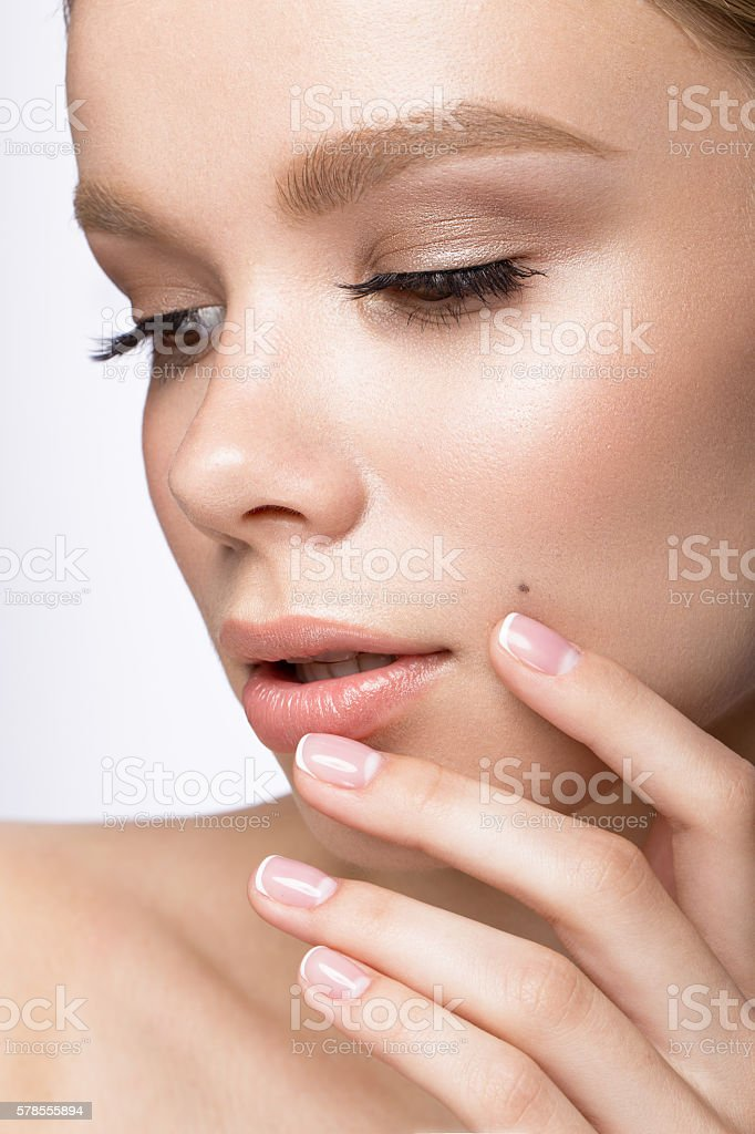 Beautiful young girl with  light natural make-up and French manicure. stock photo