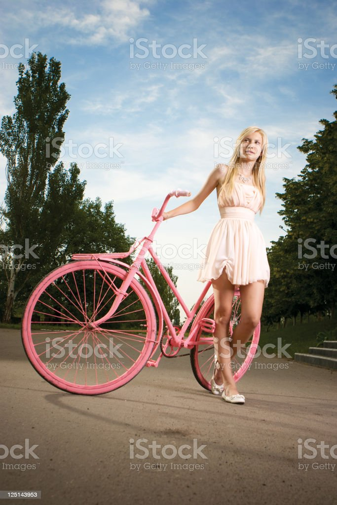 Beautiful young girl with vintage bicycle painted in pink color royalty-free stock photo