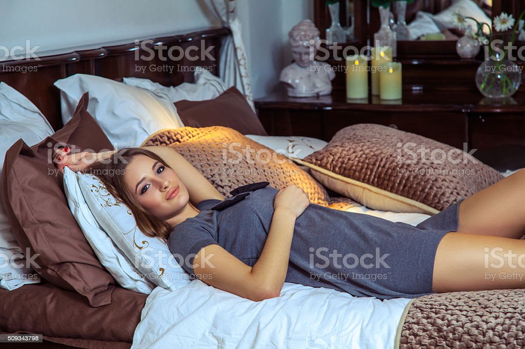Beautiful young happy fashion caucasian model  posing on bed. stock photo