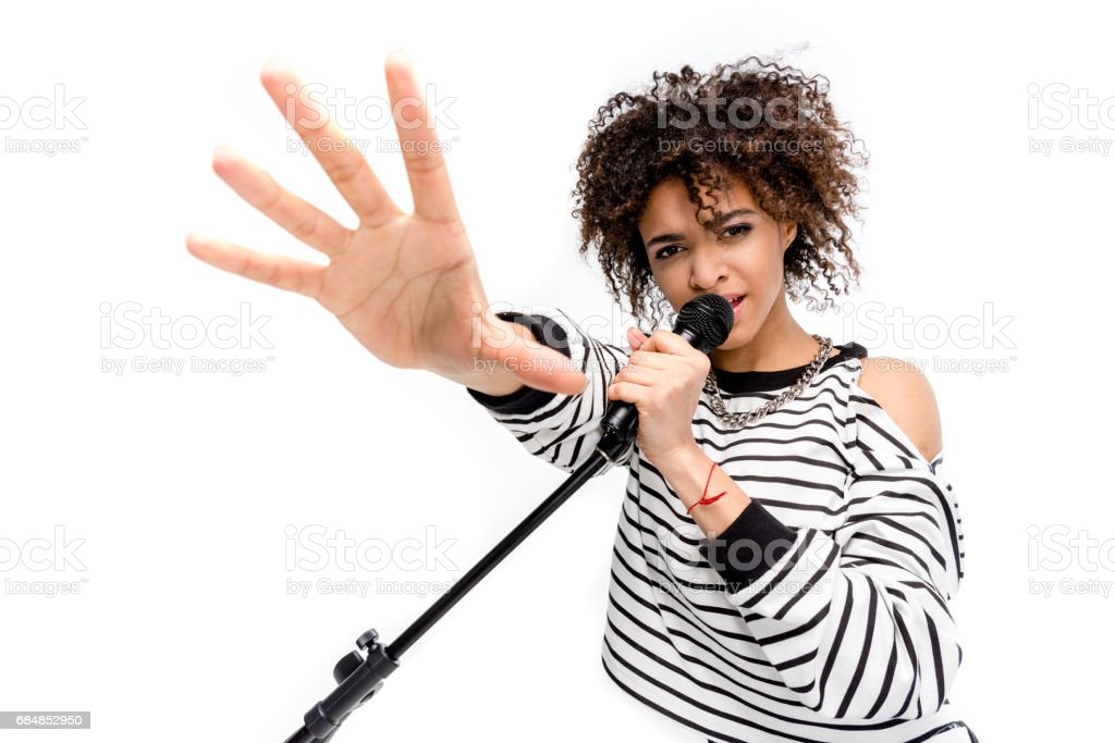 Beautiful young heavy metal singer with microphone singing and gesturing isolated on white stock photo