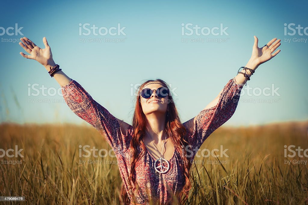 Beautiful young hippie woman sitting in a field and praying stock photo