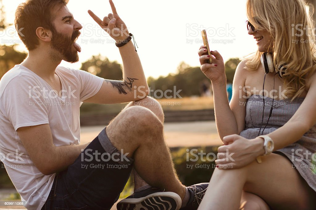 Beautiful young hipster couple using technology outdoors stock photo