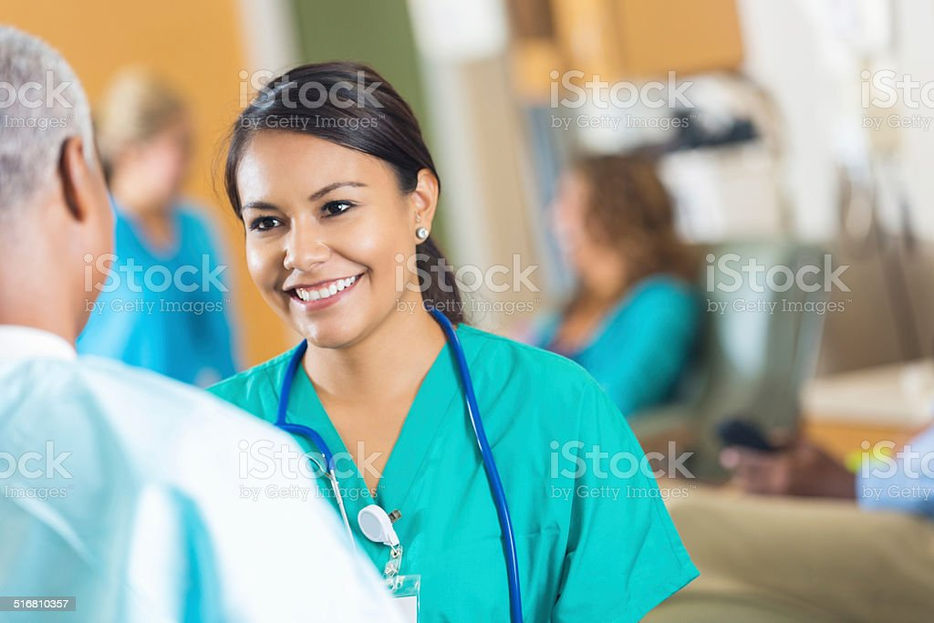 Beautiful young hospital nurse talking with senior female doctor stock photo