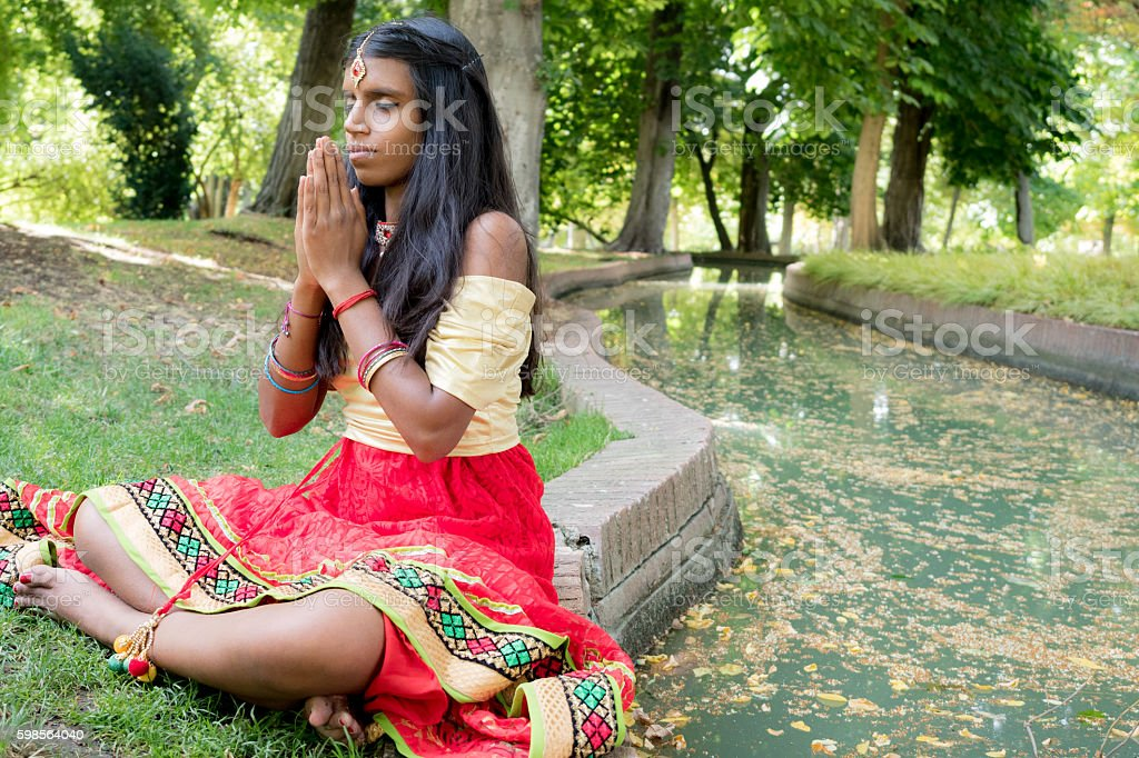 Beautiful young indian woman praying in the park. stock photo