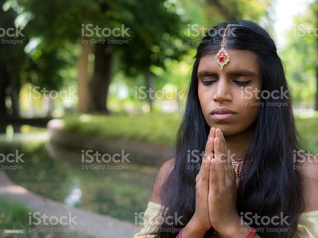 Beautiful young indian woman praying in the park stock photo