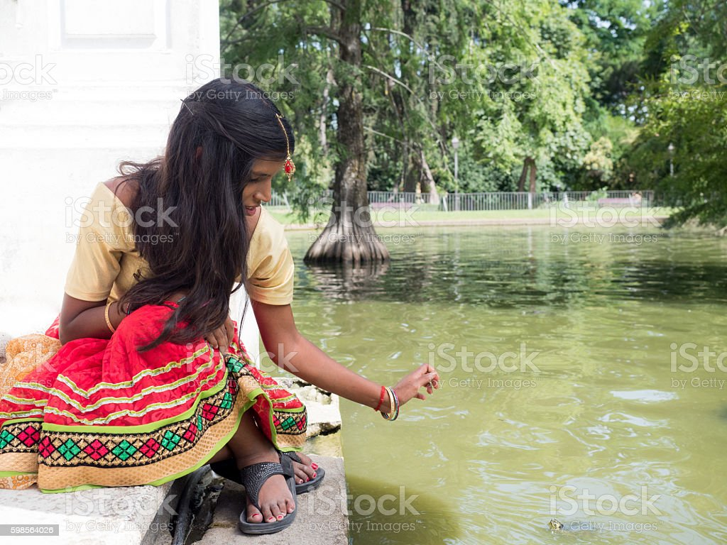 Beautiful young indian woman sitting and playing at stock photo