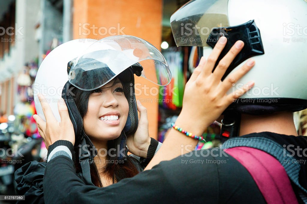 Beautiful young Indonesian couple placing each other's helmets stock photo