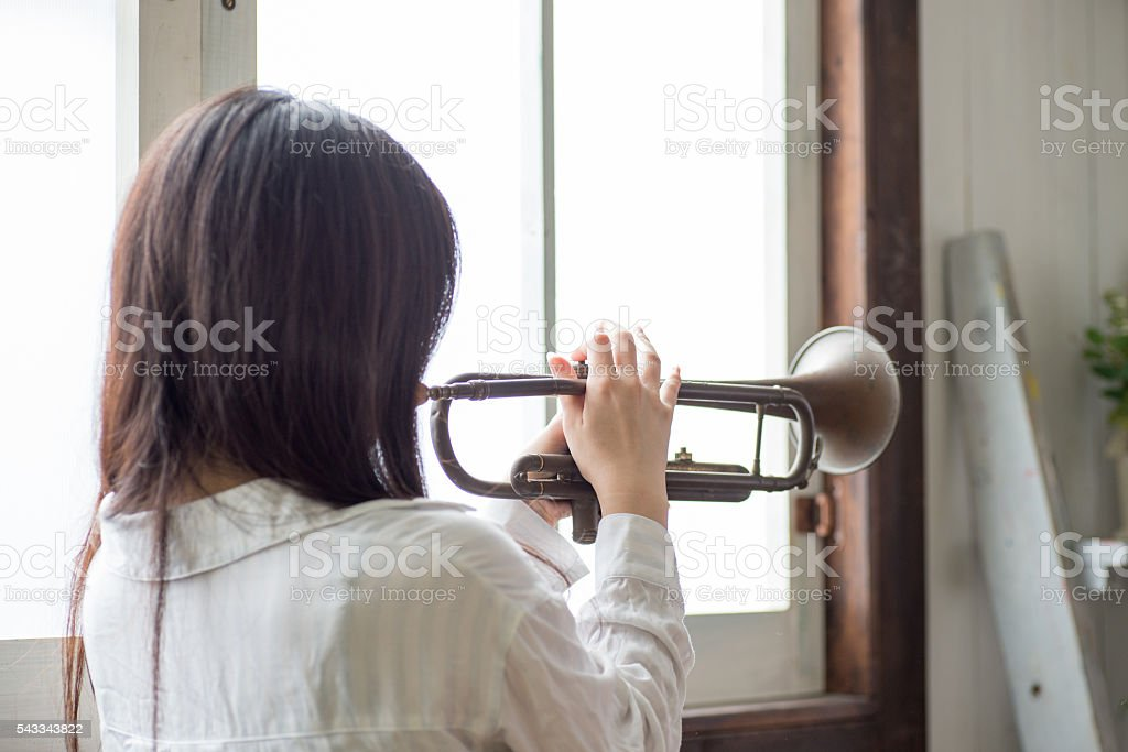Beautiful Young Japanese Woman is practicing trumpet stock photo