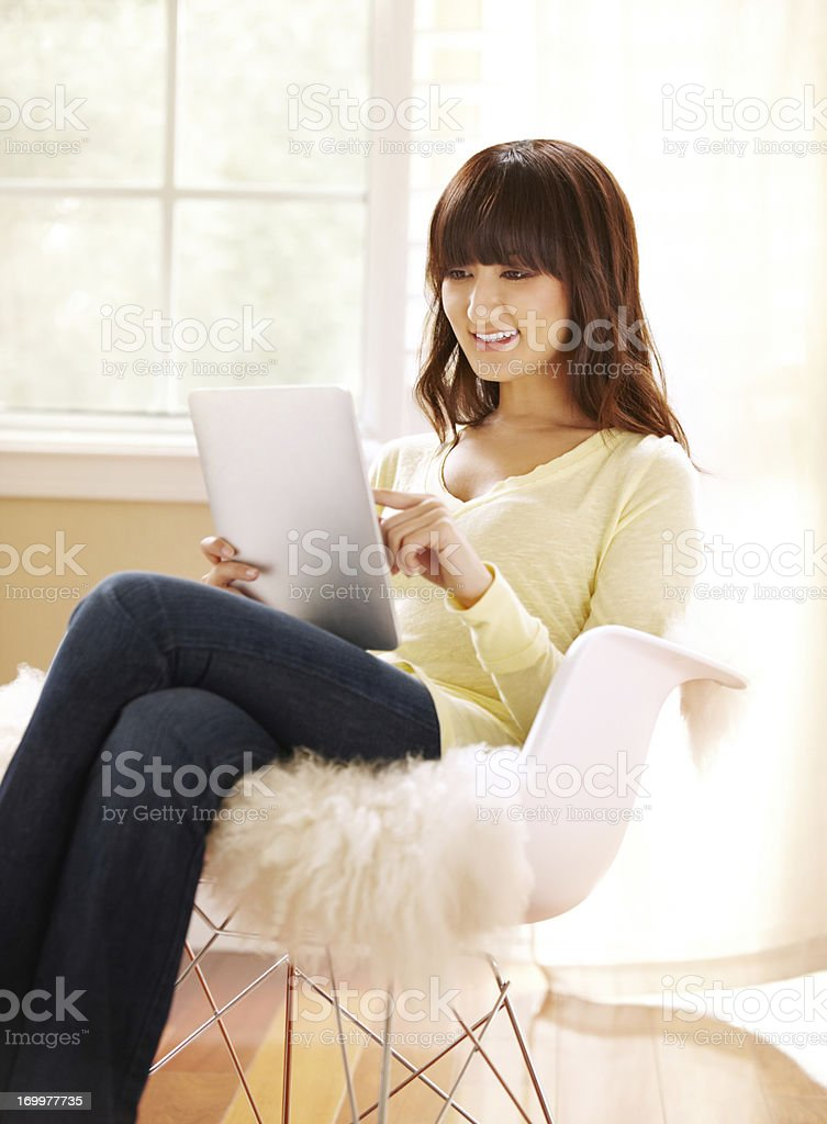 Beautiful young Japanese woman using tablet at home stock photo