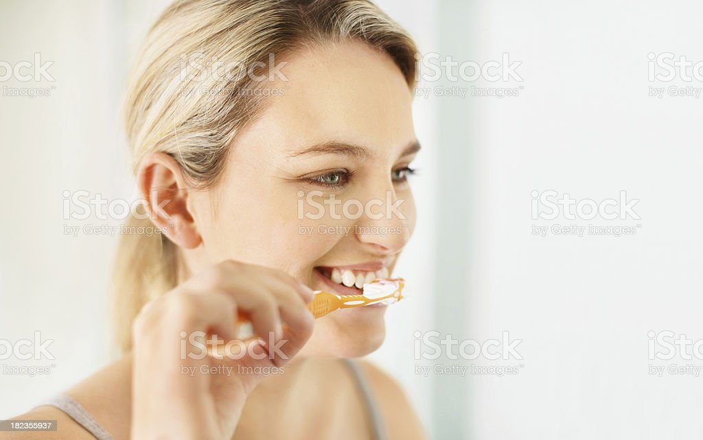 Beautiful young lady brushing her teeth royalty-free stock photo
