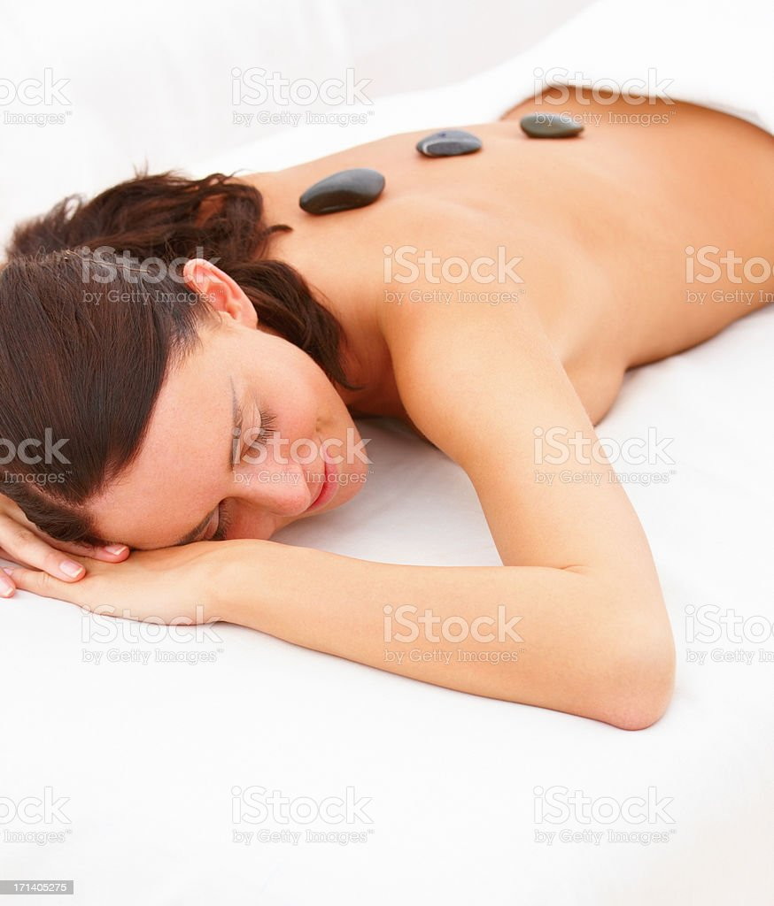 Beautiful young lady have hotstone massage at spa isolated on white stock photo