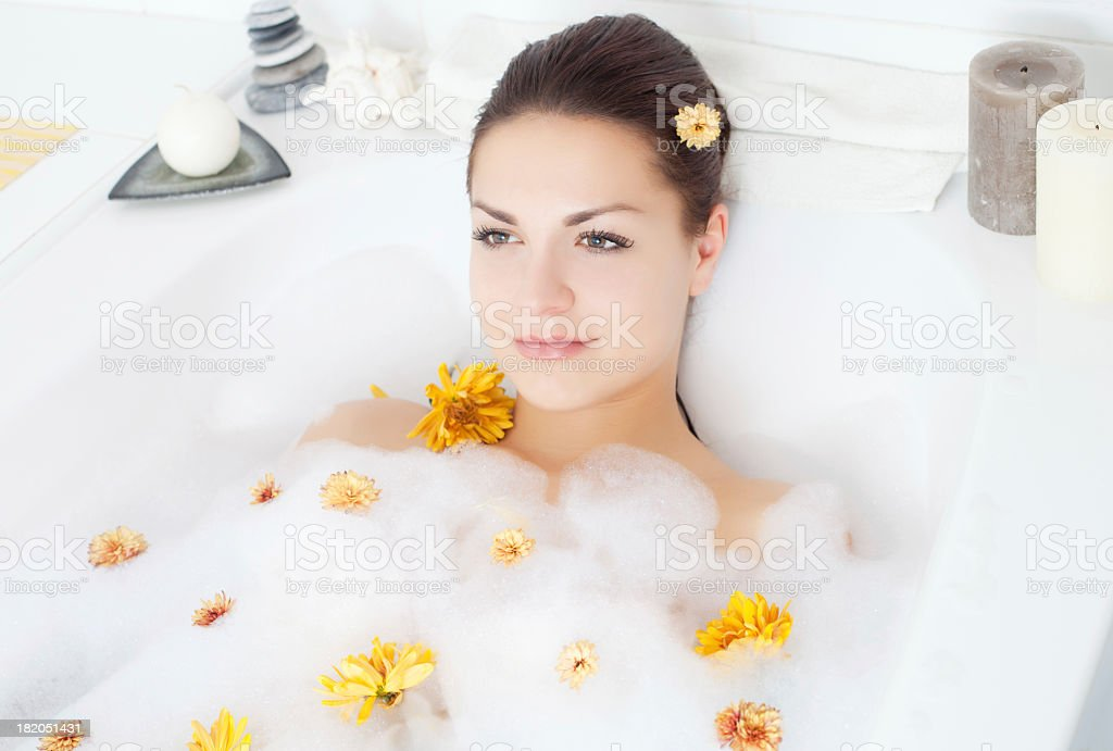 Beautiful young lady relaxing in flowered bathtub royalty-free stock photo