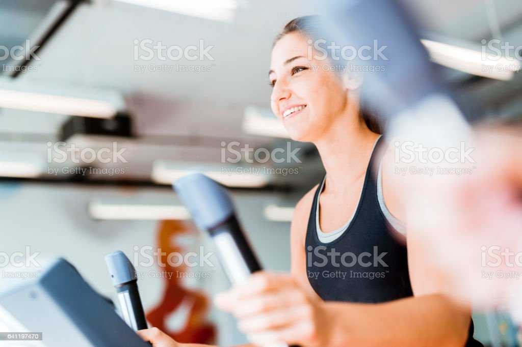 Beautiful young lady using the elliptical trainer stock photo