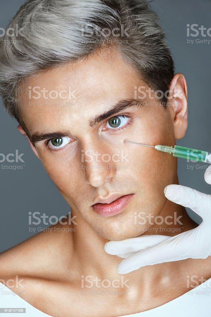 Beautiful young man gets beauty injection stock photo