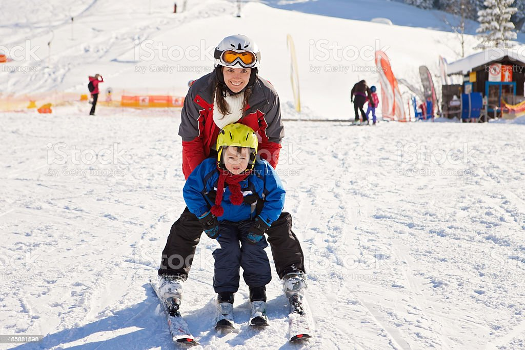 Beautiful young mom and her toddler boy, skiing the mountains stock photo