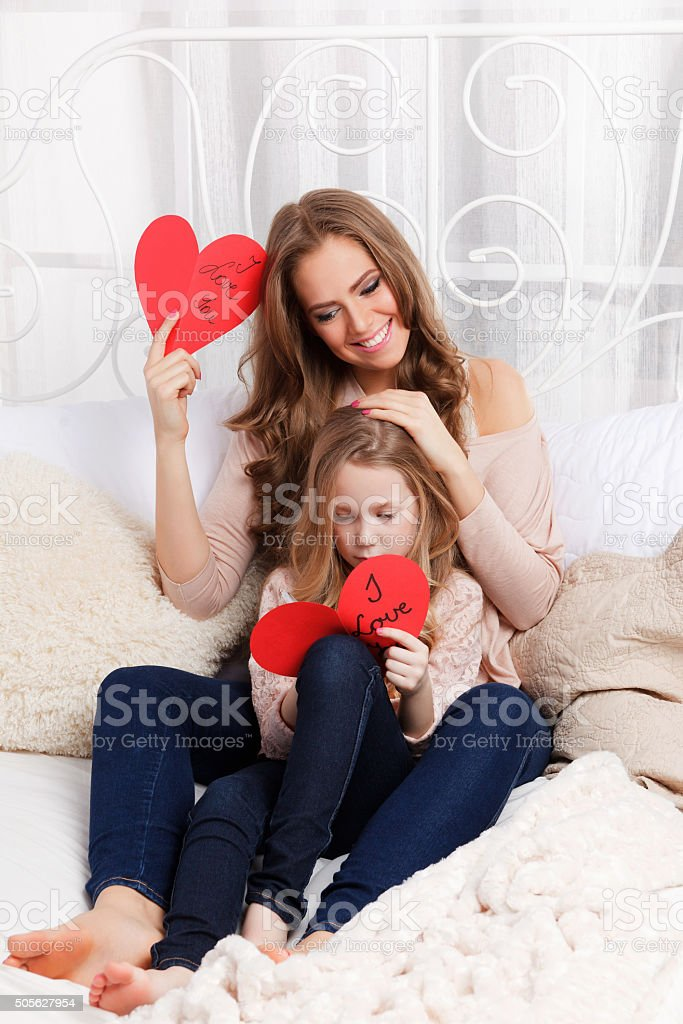 Beautiful young mother and daughter in the bed stock photo