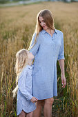 beautiful young mother and her daughter at the wheat field