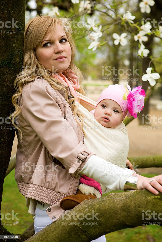 Beautiful young mother with her baby daughter in a garden royalty-free stock photo