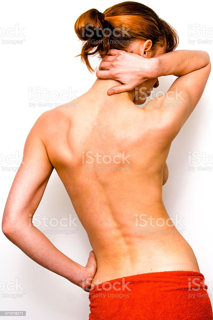 Beautiful young naked woman massaging her neck stock photo