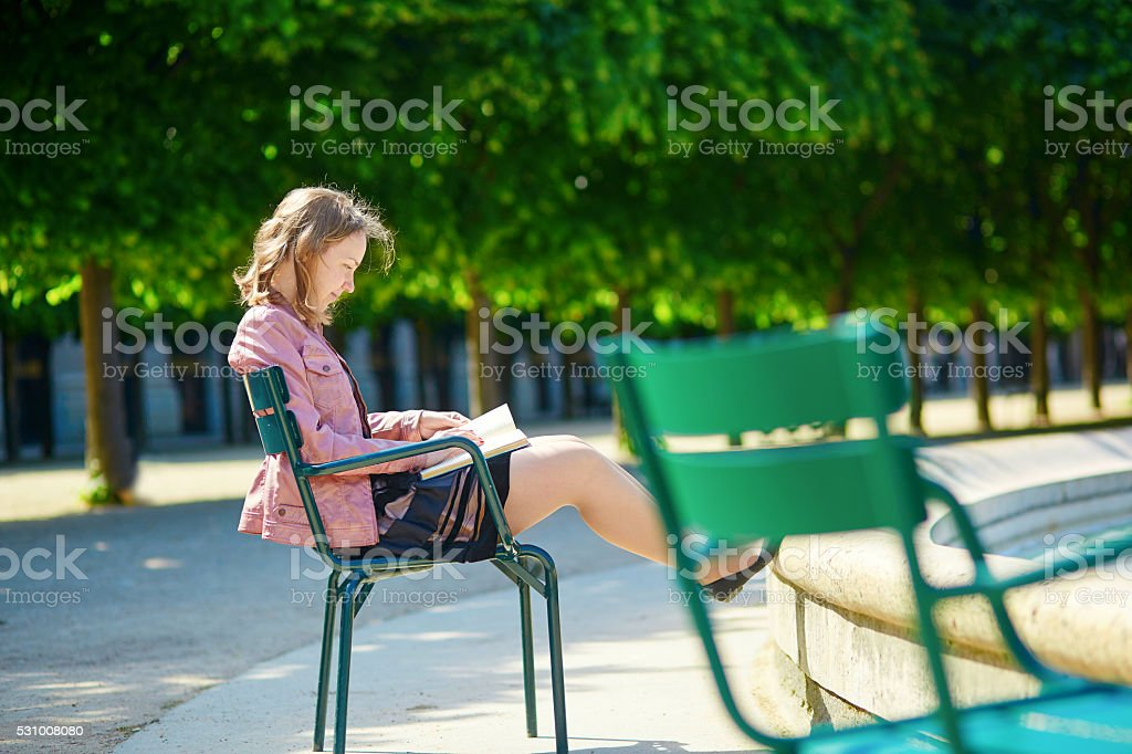 Beautiful young Parisian woman reading a book stock photo