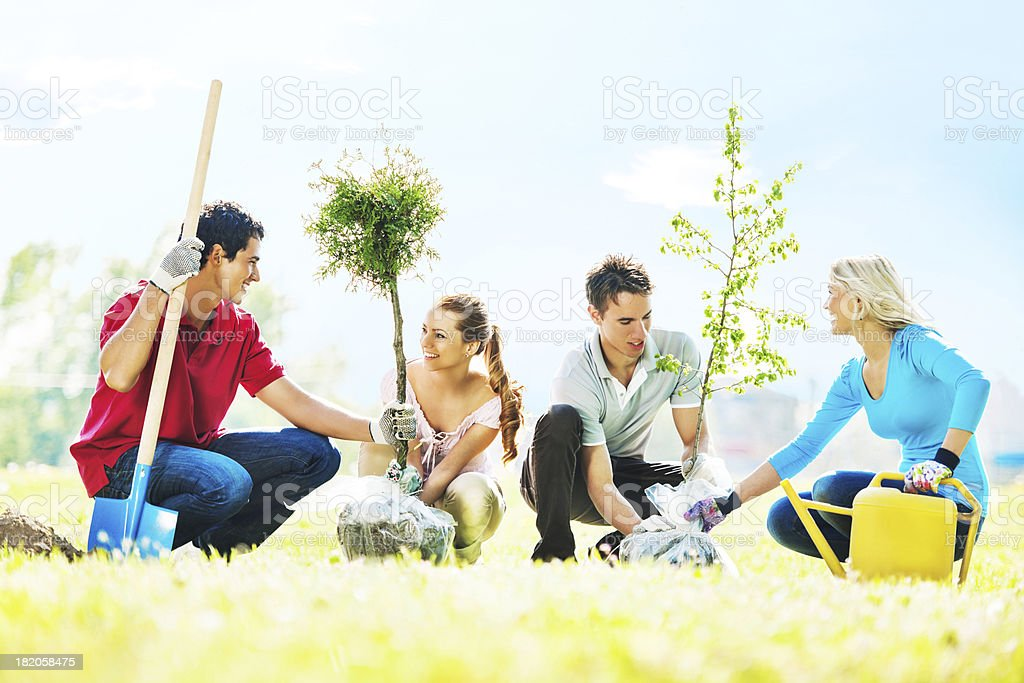 Beautiful young people planting trees. stock photo