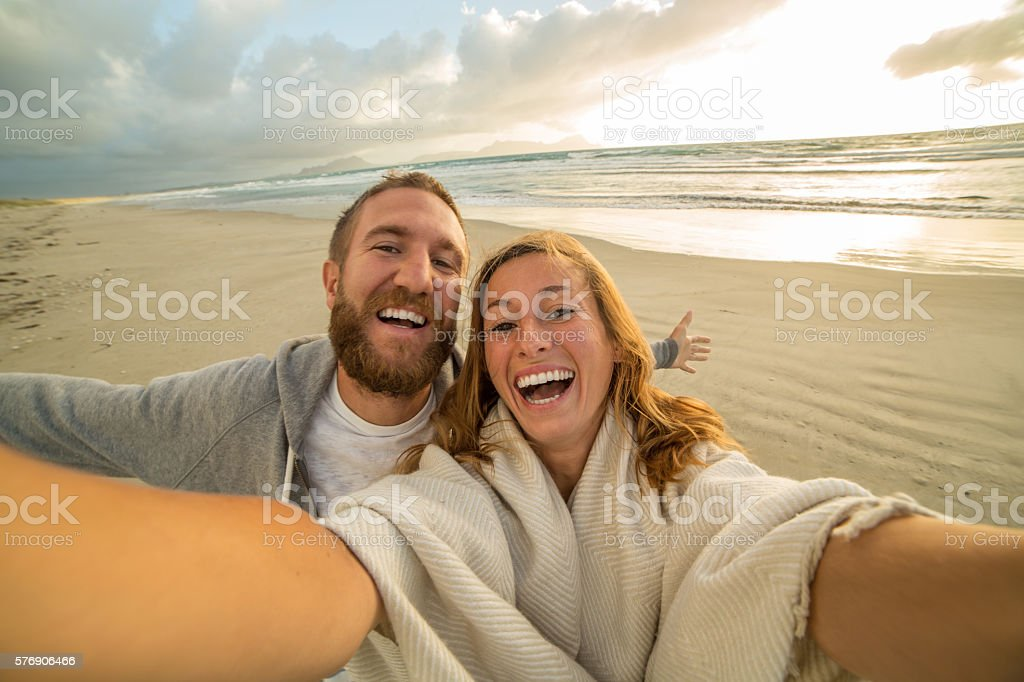 Beautiful young people take selfie portrait on the beach stock photo