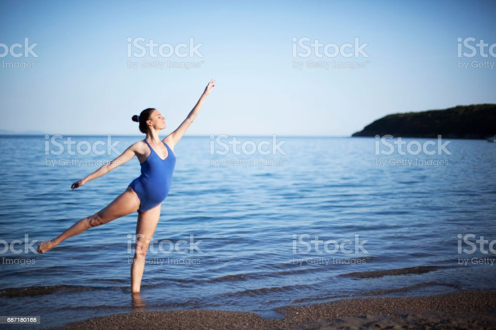 Beautiful young pregnant ballerina dancing on the beach stock photo