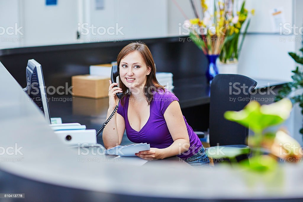Beautiful young receptionist at work stock photo