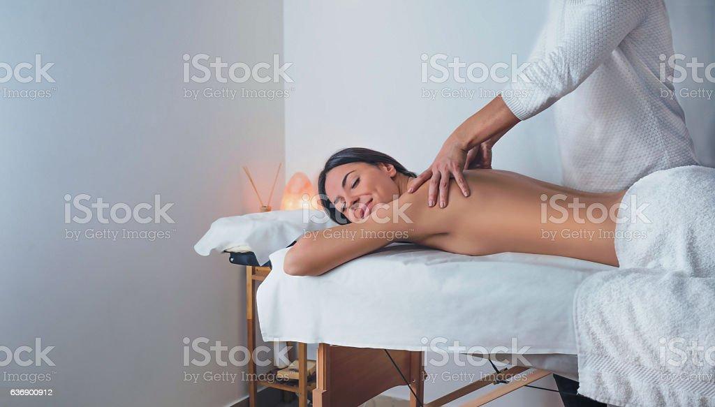 Beautiful young relaxed brunette woman enjoying back massage stock photo
