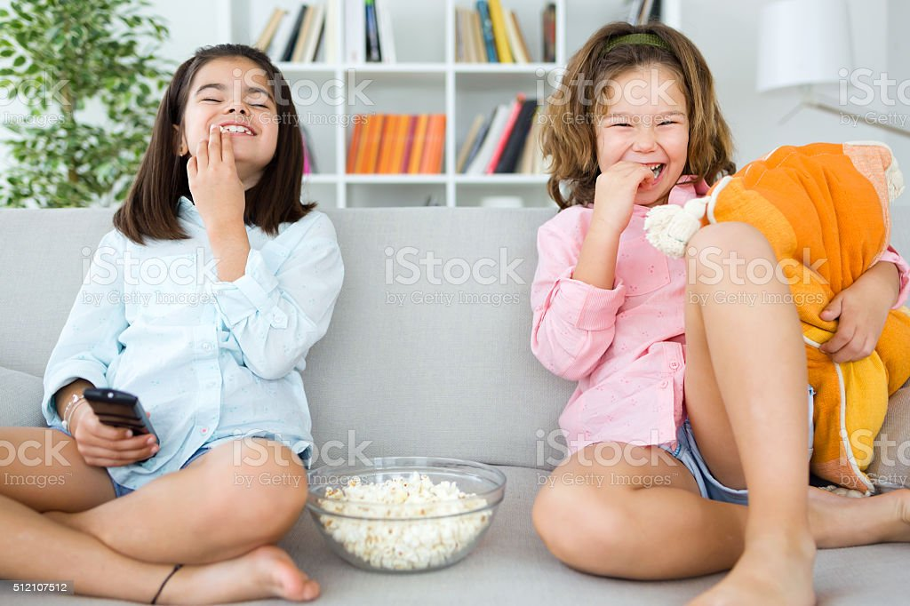 Beautiful young sisters eating popcorns at home. stock photo