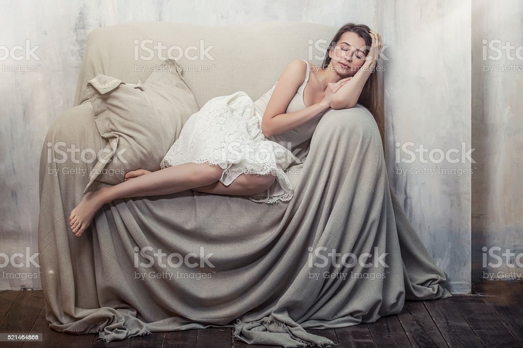 Beautiful young slim woman sleeping in a huge comfortable chair stock photo