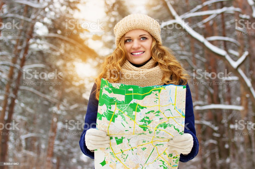 Beautiful young smiling girl holding a map in the forest, wearing blue jacket. Travel girl. stock photo