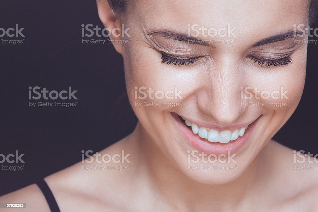 Beautiful young smiling woman with visible wrinkles around her eyes stock photo
