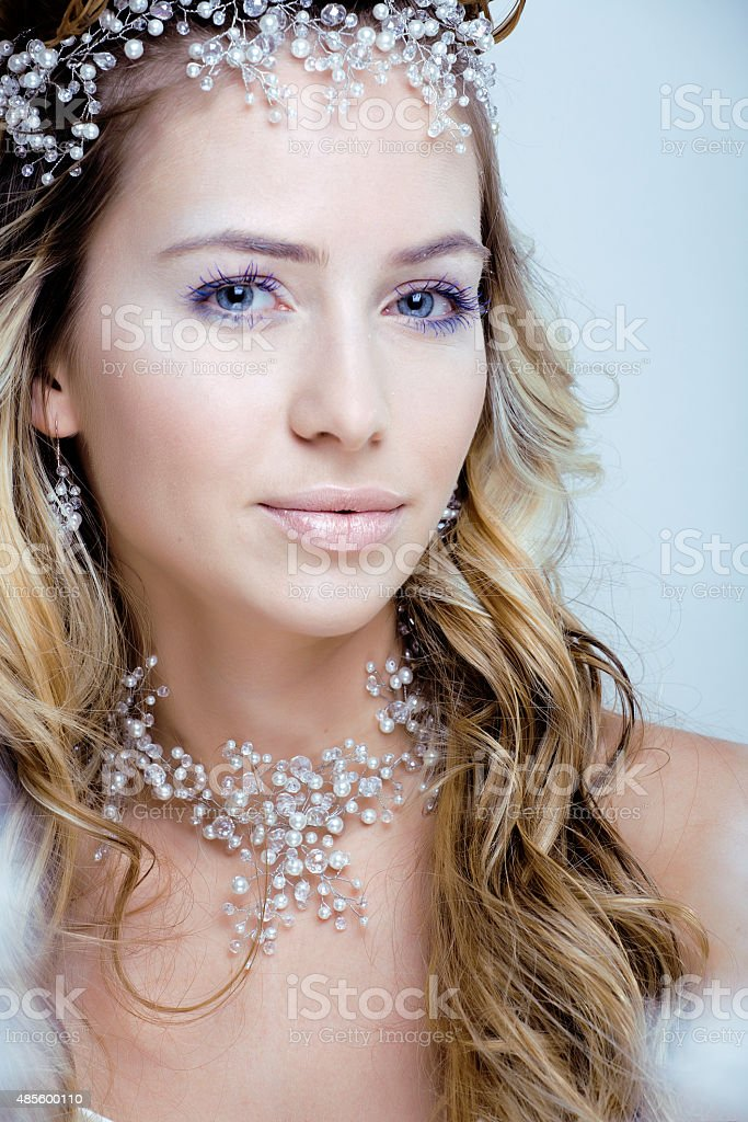 Beautiful young snow queen make up and jewelry ice toned stock photo