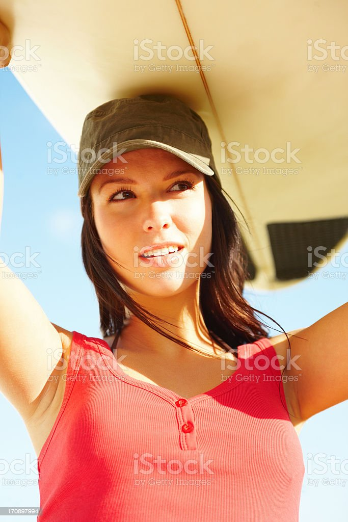 Beautiful young surfer chick carrying board royalty-free stock photo