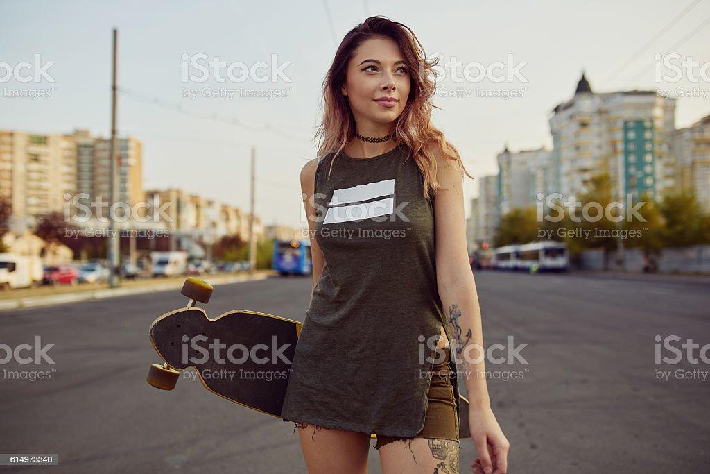 Beautiful young tattooed girl with longboard in sunny weather stock photo