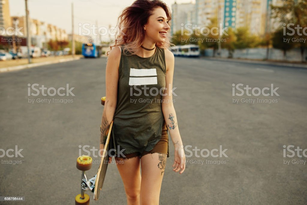 Beautiful young tattooed girl with longboard in sunny weather stock photo