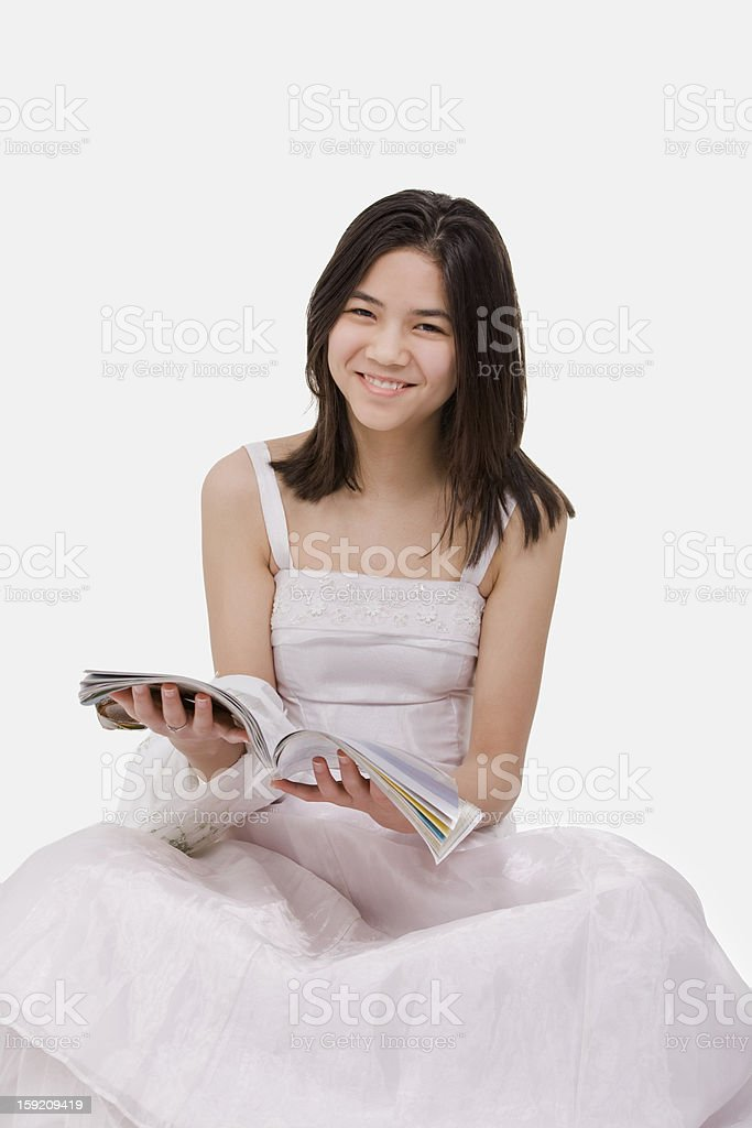Beautiful young teen girl in white dress sitting reading magazine royalty-free stock photo