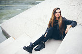 Beautiful young teenage girl is sitting on the concrete steps.
