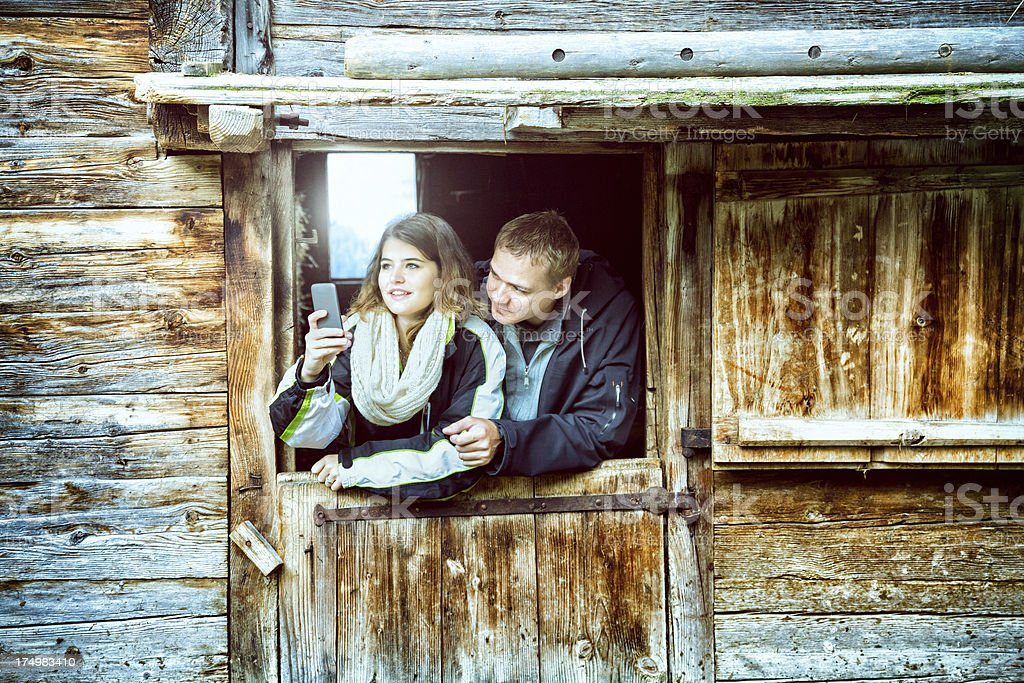 Beautiful young tourist couple taking photographs at Swiss farm royalty-free stock photo