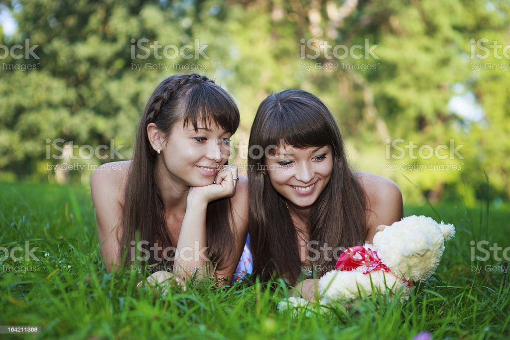 Beautiful young twins sisters in a summer green park royalty-free stock photo