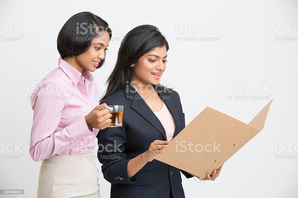 Beautiful young two Indian Businesswomen posing with document stock photo