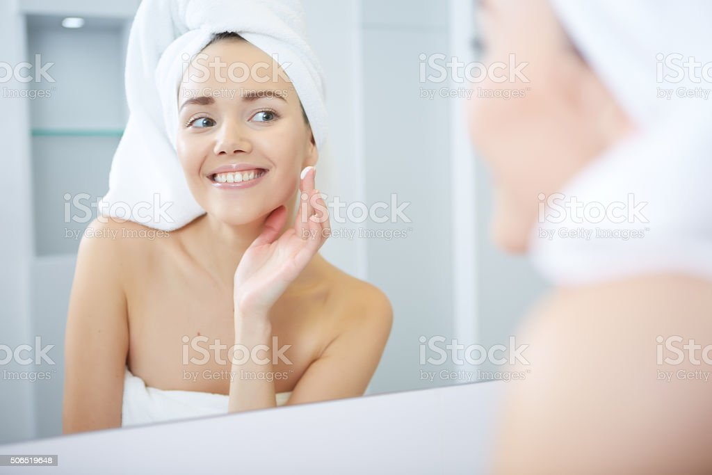 Beautiful Young Woman applying facial moisturizing cream.Skincare concept stock photo