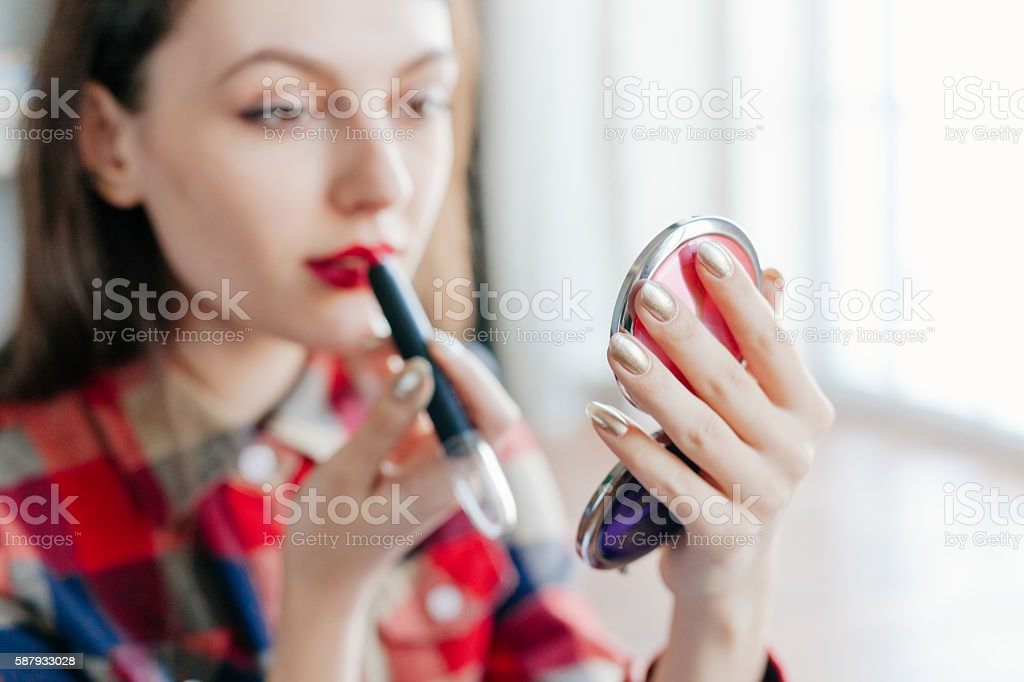 beautiful young woman applying her make-up in the mirror stock photo