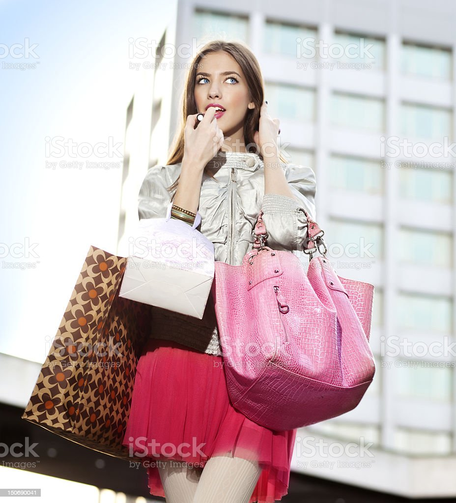 Beautiful young woman applying lipgloss stock photo