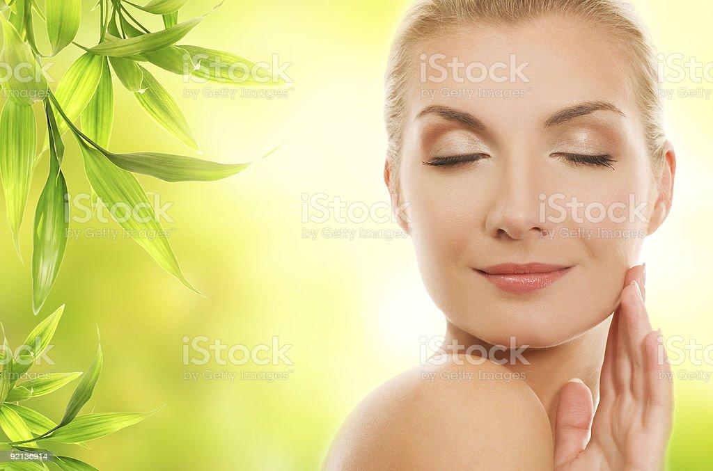 Beautiful young woman applying organic cosmetics to her skin royalty-free stock photo